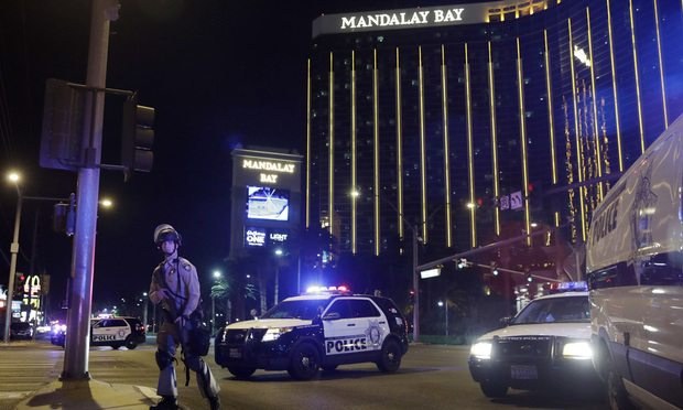 FILE - In this Sunday, Oct. 1, 2017 file photo, police officers stand along the Las Vegas Strip near the Mandalay Bay resort and casino during a shooting at a country music festival, in Las Vegas. Jay Purves and his colleagues at a private security firm manning the Route 91 Harvest festival Sunday night were a force of 200 unarmed first responders who lifted people over barriers, hid them behind pillars and under the stage, and funneled them to exits amid the panic. The guards are the first ones people inside an event go to when there is a problem. (AP Photo/John Locher, File)