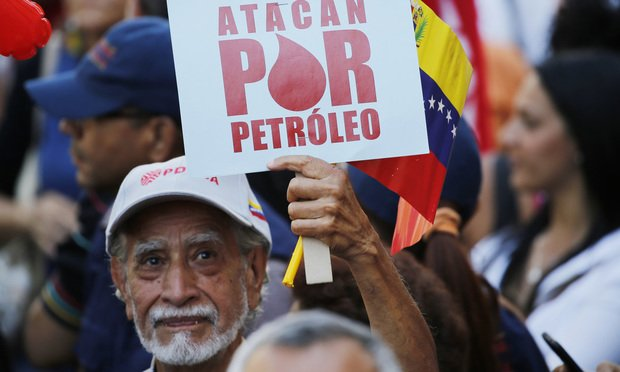 "A man holds a sign that reads in Spanish ""They attack for oil"" during a march of in support of the state-run oil company PDVSA, in Caracas, Venezuela, Thursday, Jan. 31, 2019. The government called for a mass rally to denounce U.S. sanctions against PDVSA that could starve Maduro's government of billions in export revenue but turnout was no more than a few hundred people. (AP Photo/Ariana Cubillos)"