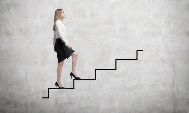 Businesswoman ascending. Credit: ImageFlow/Shutterstock.com