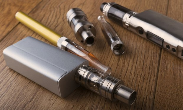Vaping pen, vape devices, mods for electronic cigarette or e-cigarette, e-cig, on a wooden background/photo courtesy of Shutterstock.com