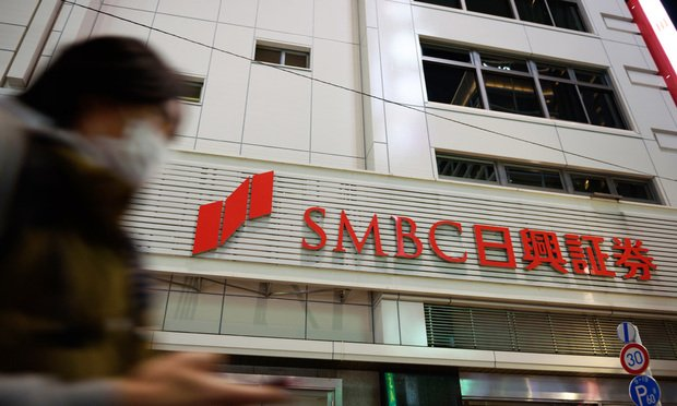 A pedestrian walks past a branch of SMBC Nikko Securities Inc., a unit of Sumitomo Mitsui Financial Group Inc.,