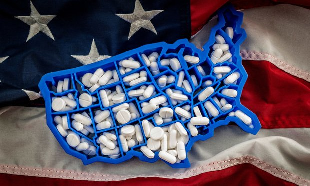 Map of USA filled with oxycodone and hydrocodone pharmaceutical pills on the American flag. Photo by Victor Moussa/Shutterstock.com