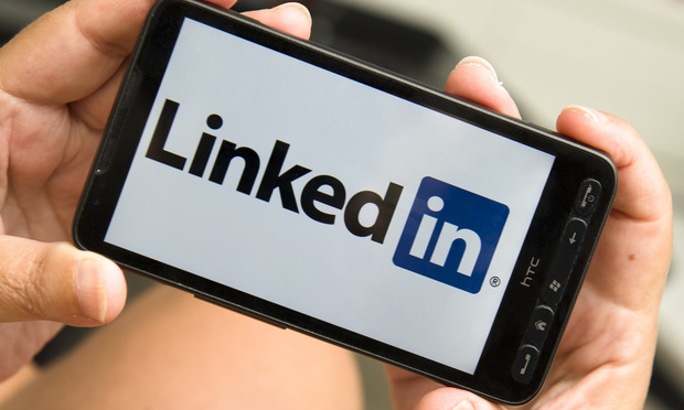 Woman holding a smartphone with linkedin logo