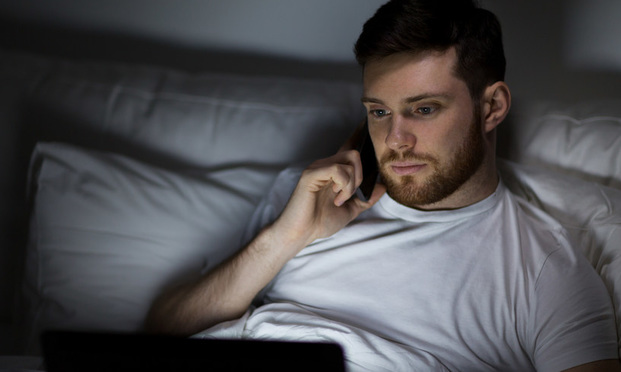 Young man on phone and computer in bed.
