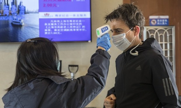 A transit worker takes the temperature of a passenger before letting him on to a ferry in Shanghai, China, on Jan. 30, 2020. Photographer: Qilai Shen/Bloomberg