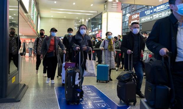 Travelers wear masks