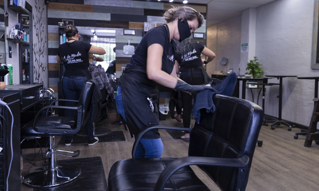A stylist wears a protective mask and gloves while sanitizing her station in between clients at A La Moda salon in Tucson, Arizona, on May 8, 2020. Photographer: Cheney Orr/Bloomberg