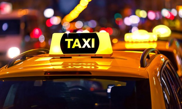 Yellow taxi cab and blurred city lights. Photo by Don Pablo/Shutterstock.com.