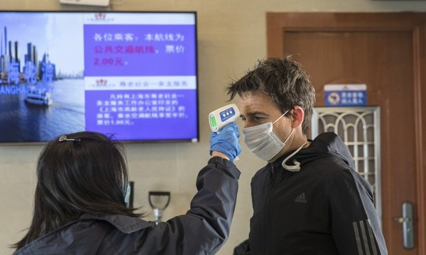 A transit worker takes the temperature of a passenger before letting him on to a ferry in Shanghai, China on Jan. 30