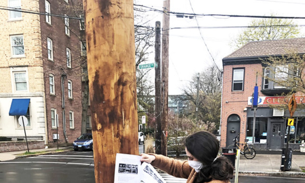 Yale Law student Hannah Abelow puts up fliers in New Haven to get the word out about law student initiatives aimed at helping the small business community in the greater New Haven area.