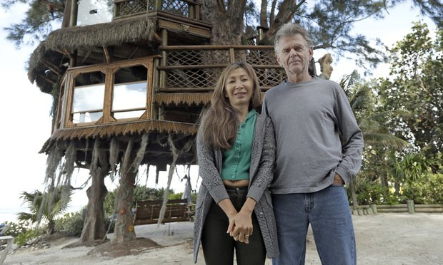 Lynn Tran and her husband Richard Hazen pose near their Australian pine treehouse in Holmes Beach, Florida. (AP Photo/Chris O'Meara)