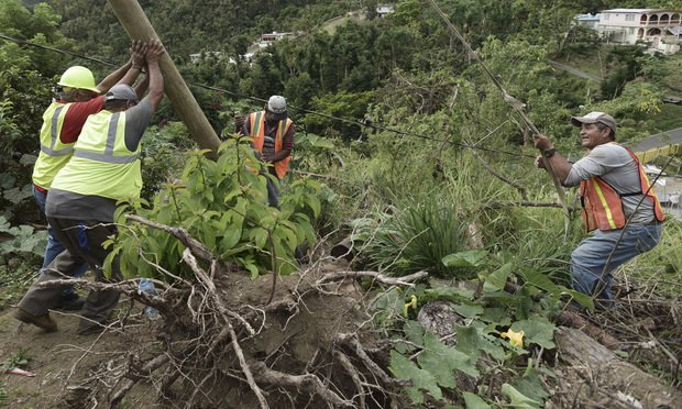 Public Works Subdirector Ramon Mendez, in hard hat, works with locals who are municipal workers as they install a new post to return electricity to a home, four months after Hurricane Maria hit the El Ortiz sector of Coamo, Puerto Rico. (AP Photo/Carlos Giusti)