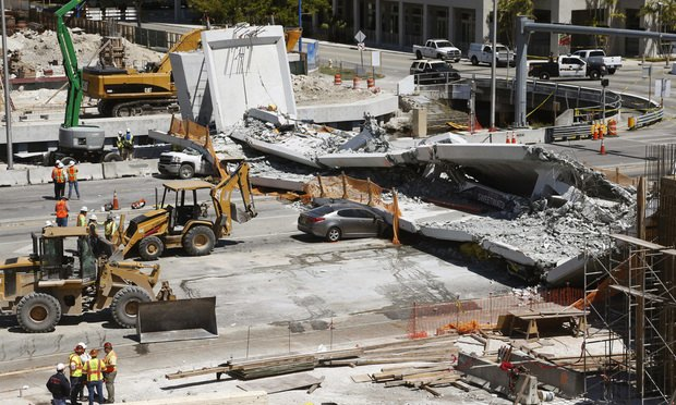 Crushed cars are shown under a section of a collapsed pedestrian bridge near Florida International University in the Miami area. (AP Photo/Wilfredo Lee)