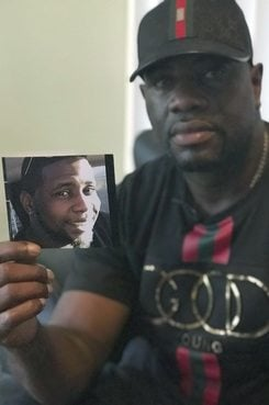 "Michael McGlockton holds a photo of his son, Markeis McGlockton, in Clearwater. Markeis was shot and killed on July 19 during an argument over a parking spot. The shooter, Michael Drejka, said he was defending himself and is using Florida's controversial ""Stand Your Ground"" defense. (AP Photo/Tamara Lush)"