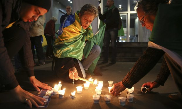 People light candles in support of Jair Bolsonaro, Brazil's presidential candidate for the National Social Liberal Party, who was stabbed during a campaign event. (AP Photo/Andre Penner)