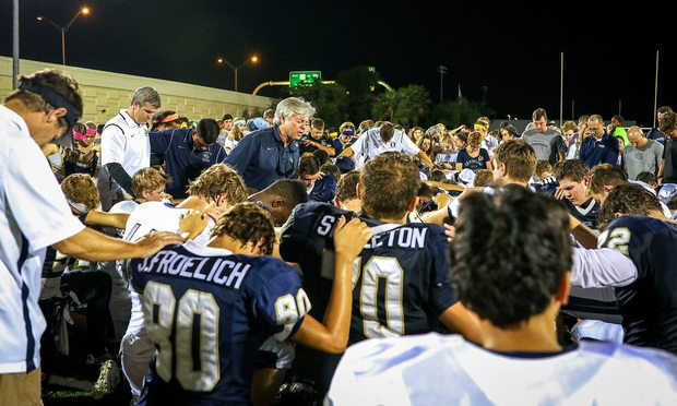 Cambridge Christian School students praying at high school football game. Photo by Beth Dare Photography/First Liberty Institute