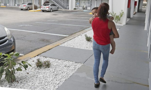 Idalis Fernandez walks to her hotel room provided by FEMA with her son Adrian, 2, at the Baymont Inn in Kissimmee. (AP Photo/John Raoux)