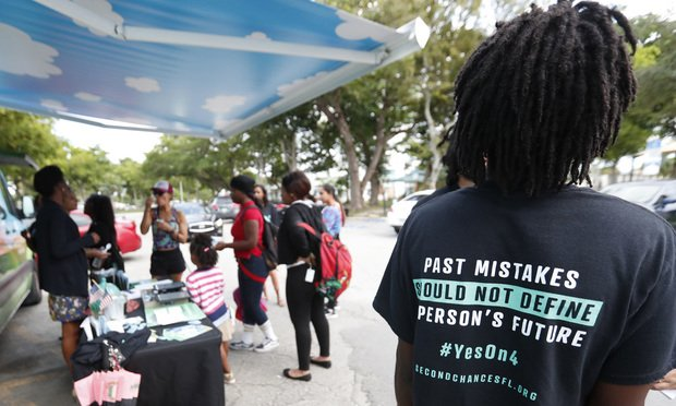 """In this Oct. 22, 2018 file photo, people gather around the Ben & Jerry's """"Yes on 4"""" truck as they learn about Amendment 4 and eat free ice cream at Charles Hadley Park in Miami. (AP Photo/Wilfredo Lee, File)"""