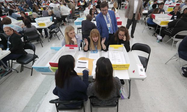 In this Nov. 16, 2018, file photo workers at the Broward County Supervisor of Elections office show Republican and Democrat observers ballots during a hand recount in Lauderhill, Fla. (AP Photo/Wilfredo Lee, File)