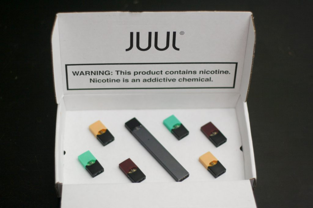 Juul electronic cigarette and packaging with nicotine warning.