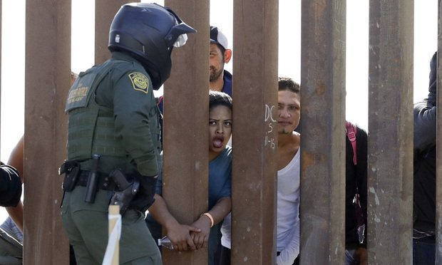 Migrants from Central America talking to a U.S. Border Patrol Agent through a border wall in San Diego.