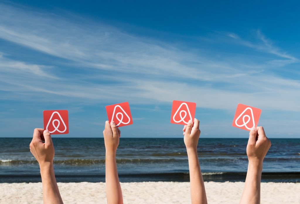 Tourists with printed cards of Airbnb logo. Photo: AlesiaKan/Shutterstock.com