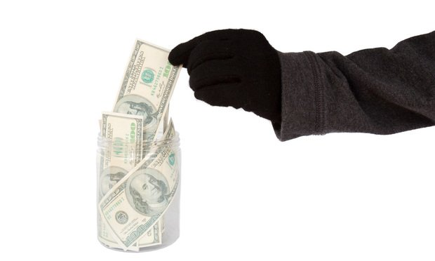 Hand with black glove taking money from the cookie jar. Photo: BeeBright/Shutterstock