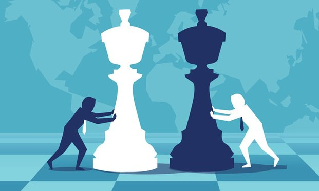 Businessmen pushing giant chess pieces.Photo: Royalty free,