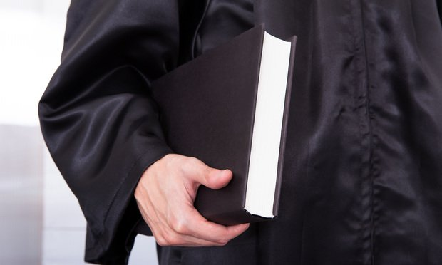 Judge in robe carrying book. Photo: Andrey_Popov/Shutterstock.com.