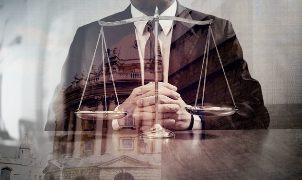 Man in a suit facing scales of justice. Photo: Shutterstock.com