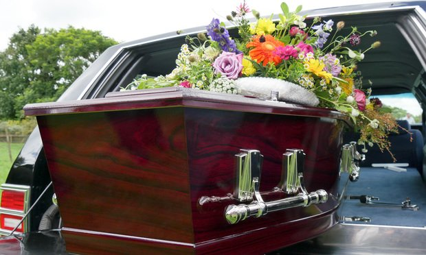 A hearse carrying a coffin. Photo: NKM999/Shutterstock.com