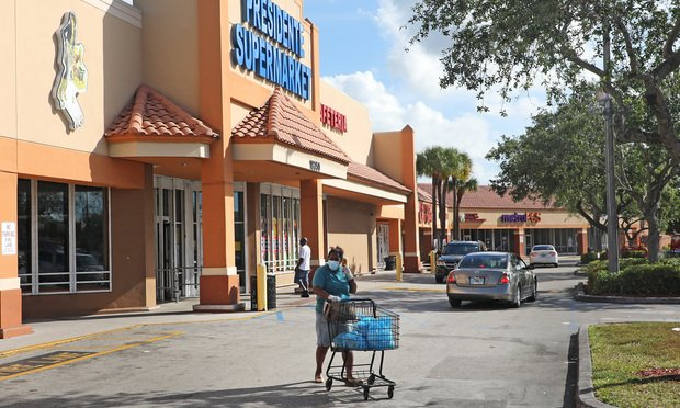 A shopper, wearing a protective mask for COViD-19, walks out of Presidente Supermarket at 18350 NW 7th Ave at Miami Gardens Shopping Center.