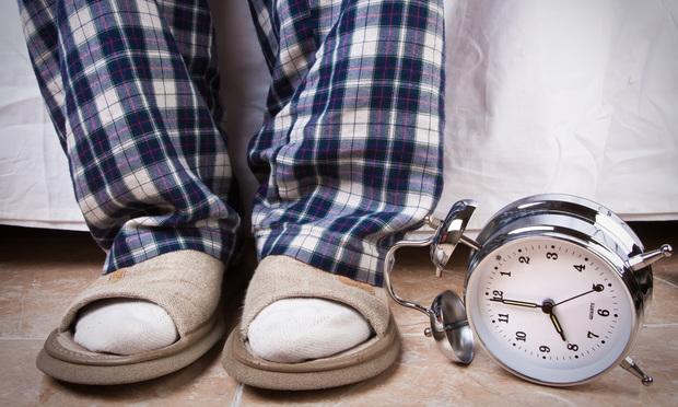 Alarm clock in the floor near an recently awake man. Photo: Shutterstock.com