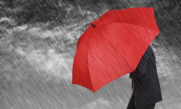 Businessman shielding himself from storm with umbrella. Photo: Brian Jackson/Fotolia (income client case intake)