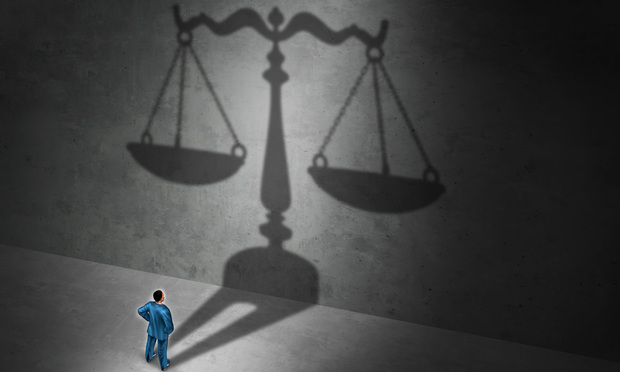 Lawyer before the scales of justice. Photo: Lightspring/Shutterstock.com