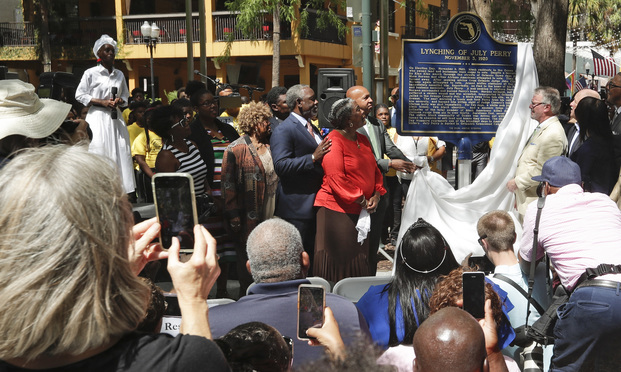 Descendants of July Perry along with local elected officials and residents attend a ceremony unveiling a historical marker in Orlando. Perry was lynched by a white mob after helping a friend trying to vote. After Perry was lynched, the mob laid siege to the black section of Ocoee killing dozens. (AP Photo/John Raoux, File)