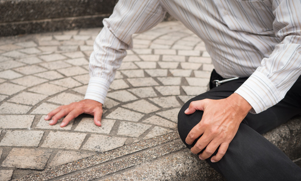 Manholding knee after falling on pavement. Credit: 9nong/Shutterstock.com.