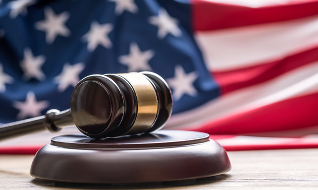 Judge's wooden gavel with USA flag in the background. Photo: Judge's wooden gavel with USA flag in the background. Photo: Marian Weyo/Shutterstock.