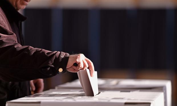 Hand casting a vote. Credit: roibu/Shutterstock.com