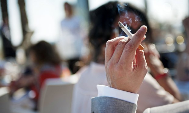 A man's hand smoking a cigarette in public. Photo: ShotShare/iStockphoto.com