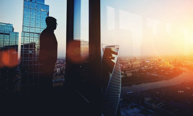 Silhouette of young intelligent man managing director resting after late business meeting while standing near big office window background with copy space for your text message or promotional content, city, city skyline, view