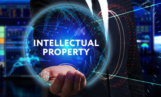 Business, Technology, Internet and network concept. Young businessman working in the field of the future, he sees the inscription: intellectual property IP