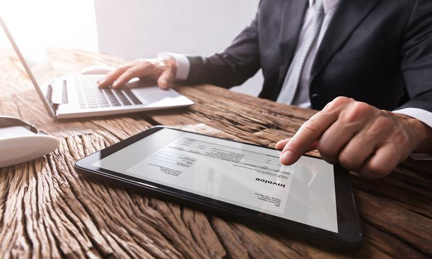 Businessman working with invoice on digital tablet.