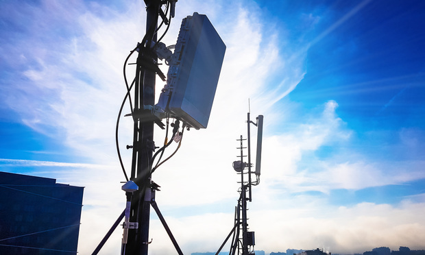 Silhouette of 5G smart cellular network antenna base station on the telecommunication mast.