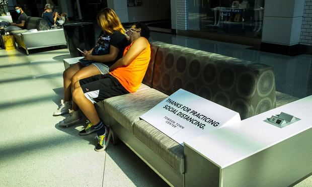 Les gens s'assoient à côté d'un panneau nécessitant une distanciation sociale en raison du COVID-19 à l'intérieur du centre commercial Towson Town Center à Baltimore, MD. 9 août 2020.