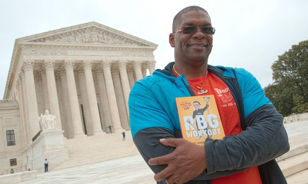 Bryant Johnson, personal trainer for Supreme Court Justice Ruth Bader Ginsburg poses in Washington, Friday, Oct. 13, 2017, with his new book, &quot;The RBG Workout: How She Stays Strong ... and You Can Too!&quot; <i>Credit: AP Photo/J. Scott Applewhite</i>