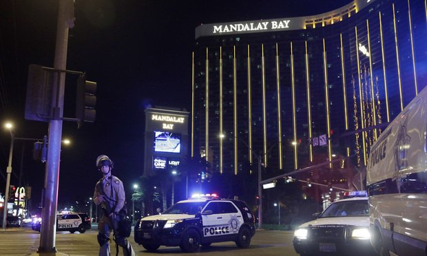 In this Sunday, Oct. 1, 2017 file photo, police officers stand along the Las Vegas Strip near the Mandalay Bay resort and casino during a shooting at a country music festival, in Las Vegas. Jay Purves and his colleagues at a private security firm manning the Route 91 Harvest festival Sunday night were a force of 200 unarmed first responders who lifted people over barriers, hid them behind pillars and under the stage, and funneled them to exits amid the panic. The guards are the first ones people inside an event go to when there is a problem. (AP Photo/John Locher, File)