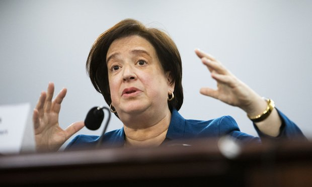 Supreme Court Justice Elena Kagan gestures in front of a podium
