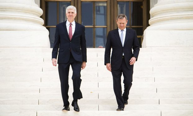 ssociate U.S. Supreme Court Justice Neil Gorsuch, left, and Chief Justice John Roberts Jr., right, walk down the steps of the U.S. Supreme Court after holding an Investiture ceremony for Justice Gorsuch, on June 15, 2017.