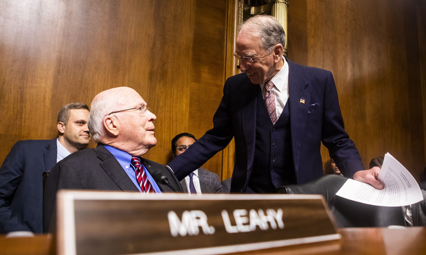 Senator Patrick Leahy speaking with Senator Charles Grassley.